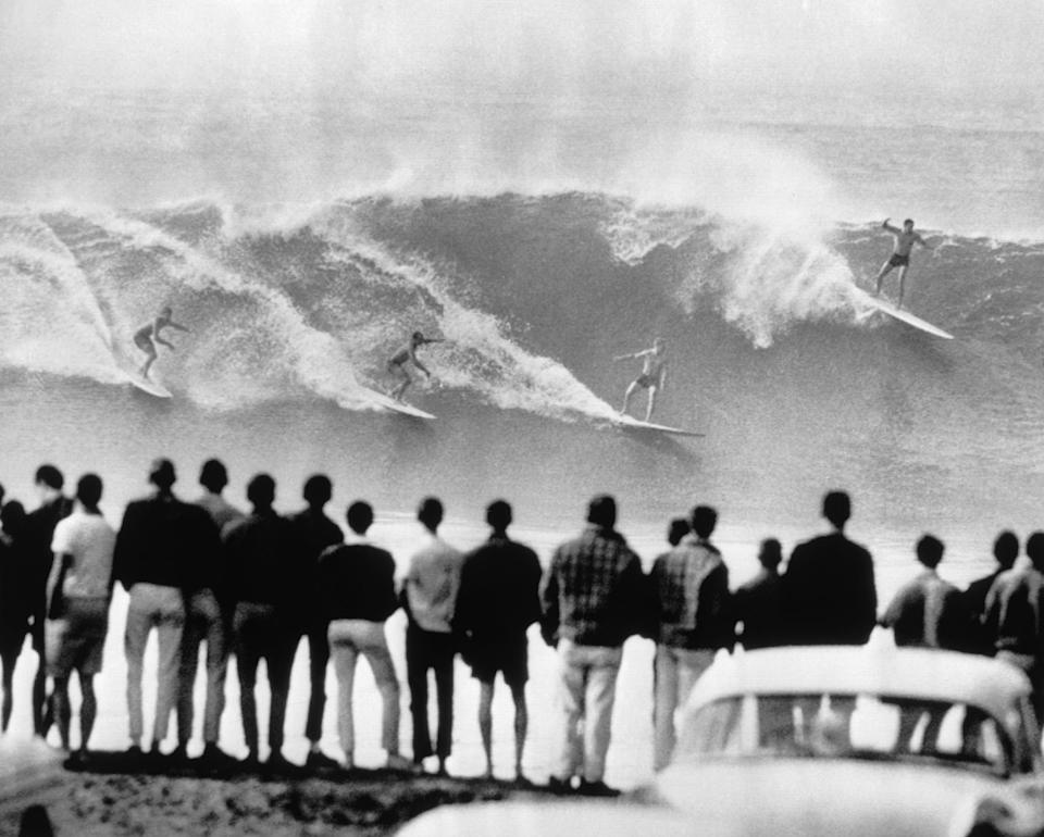 File- this Dec. 1962 file photo shows a crowd on shore watching at Redondo Beach, Los Angeles, four surfing enthusiasts. It was a land of perfect waves and sparkling sand, in a place where there was a beach party every night and summer never ended. (AP Photo, File)