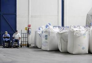 Workers sit next to bags containing sugar at the San Francisco Ameca sugar factory in the town of Ameca