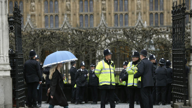 British police officers stand guard at the gate of the Houses of Parliament in London, Wednesday, April 17, 2013. The coffin containing the body of former British Prime Minister Margaret Thatcher will leave the Houses of Parliament in a hearse to St. Clement Danes Church, the RAF Chapel, to be transferred to a horse-drawn gun carriage for a procession to St. Paul's Cathedral for a service. The Iron Lady, who transformed Britain during her 11-year tenure, died April 8 at age 87. (AP Photo/Sang Tan)