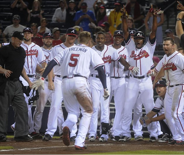 Atlanta Braves' Freddie Freeman (5) approaches home plate as team mates wait to greet him during his two run home run to win the baseball game against the New York Mets during the ninth inning, Monday
