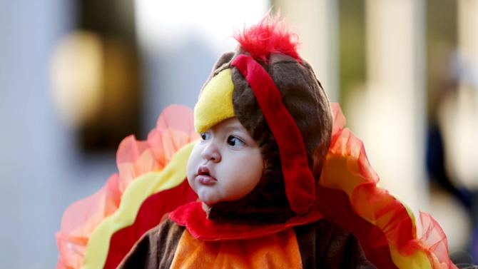Carmelo Suarez, 11-months, dresses in a turkey costume at his first 65th Annual H-E-B Thanksgiving Day Parade, Thursday, Nov. 27, 2014, in Houston. (AP Photo/Houston Chronicle, Gary Coronado)