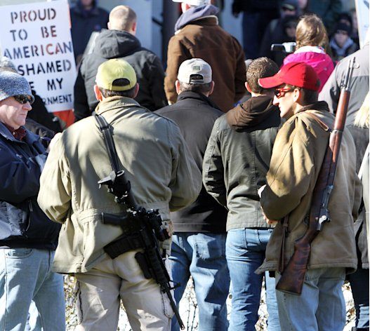 FILE - In this Thursday Jan. 31, 2013 file photo, gun owners rally to promote the right to bear arms in front of the Statehouse in Concord, N.H. Speakers criticized Democrats in Washington for favoring new gun control laws following the Connecticut school shooting that left 26 dead in December. An immigration debate is raging and a budget crisis looms in Congress, but conservative activists from New Hampshire to Colorado have seized a new rallying cry for the tea party movement: Guns. (AP Photo/Jim Cole, File)