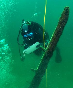 In this photo made Saturday, June 15, 2013, and released by Great Lakes Exploration Group, French underwater archaeologist Olivia Hulot jots notes while inspecting a timber jutting from the bottom of northern Lake Michigan that experts believe could be part of the long-lost ship the Griffin. Crews are digging a pit at the base of the beam to see if it's attached to a buried ship. (AP Photo/Chris Doyal, Great Lakes Exploration Group.)