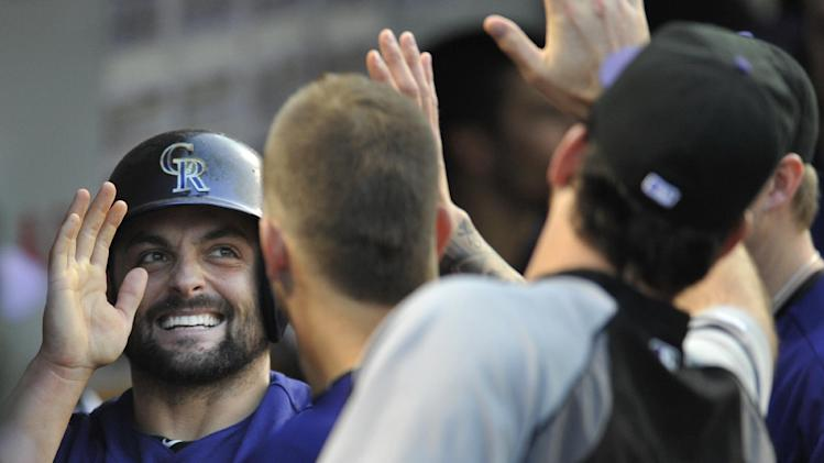 Colorado Rockies' Michael McKenry celebrates with teammates in the dugout after scoring on a Charlie Culberson double during the second inning of a baseball game against the Chicago Cubs in Chicago, Wednesday, July 30, 2014. (AP Photo/Paul Beaty)