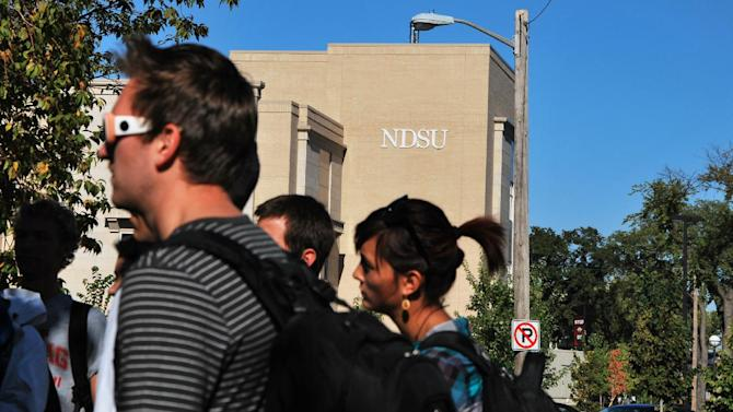 Students gather outside North Dakota State University's Klai Hall after the downtown campus, along with the main campus, was evacuated because of a bomb threat Friday Sept. 14, 2012 in Fargo.  Thousands of people streamed off university campuses in Texas and North Dakota on Friday after phoned-in bomb threats prompted evacuations and officials warned students and faculty to get away as quickly as possible. No bombs had been found on either campus by midmorning and it was not clear whether the threats were related.  (AP Photo/The Forum, J. Shane Mercer)