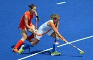 Maartje Paumen (R) of Netherlands dribbles past Zhao Yudiao of China during their London 2012 Olympic Games women's field hockey preliminary match at the Riverbank Arena in London. Reigning Olympic champions the Netherlands defeated China 1-0 on Thursday in a repeat of the 2008 women's hockey final to bolster their strong position at the London Games with a third straight win