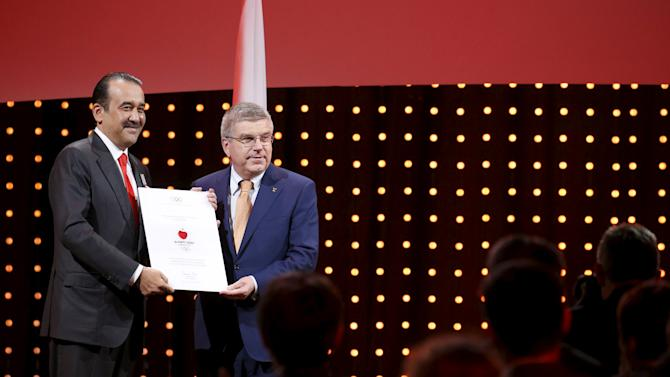 Kazakhstan's PM Massimov receives a diploma for Kazakhstan's candidature from IOC President Thomas Bach during the Almaty 2022 Presentation at the 128th IOC Session in Malaysia's capital city of Kuala Lumpur
