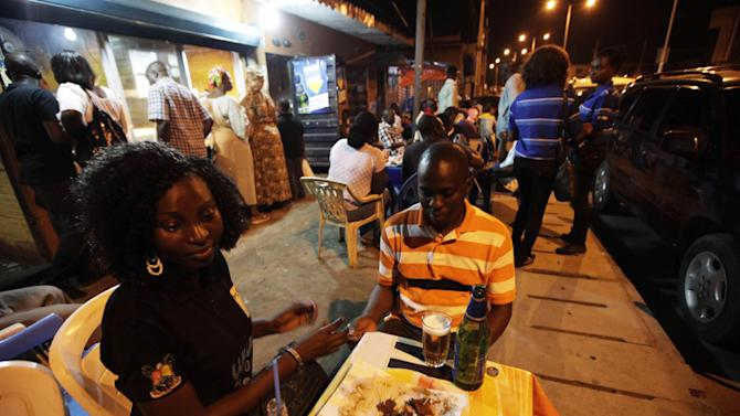 "In this photo taken on Saturday, Oct. 20, 2012, people drink beers and eat suya at night at a ""Supa Suya"" eatery in Lagos, Nigeria.  As night falls across Nigeria, men fan the flames of charcoal grills by candlelight or under naked light bulbs, the smoke rising in the air with the smell of spices and cooking meat. Despite the sometimes intense diversity of faith and ethnicity in this nation of 160 million people, that thinly sliced meat called suya, is eaten everywhere. (AP Photo/Sunday Alamba)"