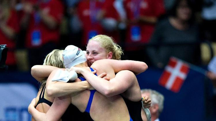 Athletes of Denmark's team celebrate after winning the women's 4x50 meters freestyle event of the Len European Short Course Swimming Championships in Herning, Denmark on December 12, 2013