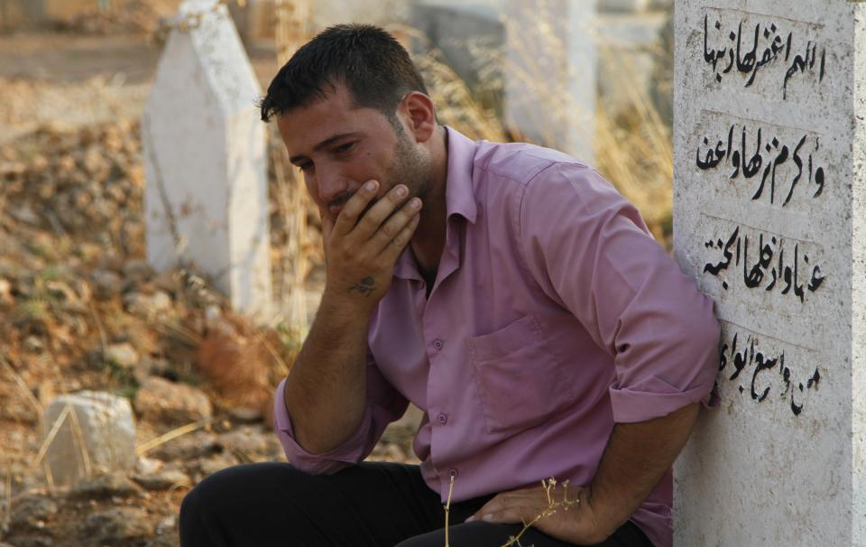 A Syrian man reacts after the funeral of 29 year-old Free Syrian Army fighter, Husain Al-Ali, who was killed during clashes in Aleppo, in the cemetery in the town of Marea on the outskirts of  Aleppo city, Syria, Thursday, Aug. 9, 2012. (AP Photo/ Khalil Hamra)