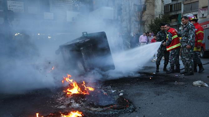 Lebanese firefighters extinguish burned tires and garbage containers that were set on fire by protesters, after two Sunni Muslim sheikhs at dar al-Fatwa, Lebanon's highest Sunni Authority, were attacked by Shiite men late Sunday, in Beirut, Lebanon, Monday March 18, 2013. A few hundred protesters held a demonstration while others blocked roads after four Sunni Muslim sheiks were assaulted in two separate incidents that inflamed sectarian sentiment in the country. Tensions have been running high in Lebanon in recent months, mainly because of the Syrian civil war raging next door. (AP Photo/Hussein Malla)