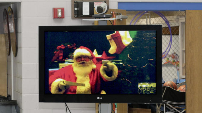 IMAGE DISTRIBUTED FOR SKYPE - Santa waves hello to children at the Queen of Angels School in Fort Wayne, Ind. via Skype. Queen of Angels was one of three recipients of a $10,000 technology makeover in Skype's Santa in the Classroom contest. (AJ Mast/AP Images for Skype)