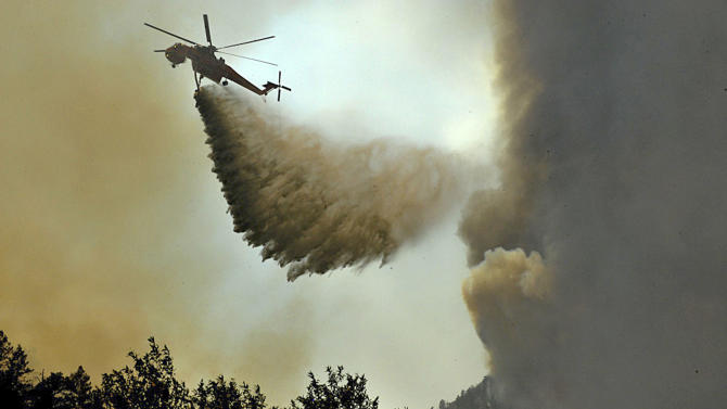 In this photo taken on Monday, June 18, 2012, and made available Wednesday by the Colorado National Guard, a helicopter drops a load of water above the High Park wildfire, about 15 miles west of Fort Collins, Colo. The fire already has destroyed at least 189 homes since it was sparked by lightning June 9. (AP Photo/Colorado National Guard , Jess Geffre)