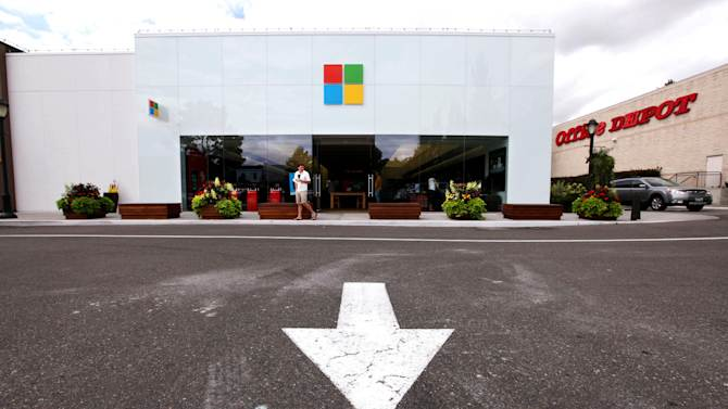 FILE - In this Thursday, Aug. 23, 2012, file photo, the new Microsoft logo is seen above the entrance to a company store in Seattle.  Microsoft Corp.'s net income fell 22 percent in the latest quarter as it deferred revenue from the sale of its upcoming Windows 8 operating system to PC makers, and as PC sales in general took a dive. The software company's net income was $4.47 billion, or 53 cents per share. That was down from $5.7 billion, or 68 cents per share, a year ago, and exceeded analyst estimates, which had been in the 50-52 cent range. (AP Photo/Elaine Thompson, File)