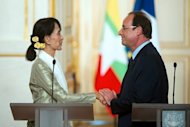 France's President Francois Hollande (R) shakes hands with Myanmar pro-democracy leader Aung San Suu Kyi after a press conference at the Elysee presidential palace in Paris. Hollande told Suu Kyi Tuesday that France would do everything possible to back the country's democratic transition, as she visited Paris for the last leg of a landmark European tour