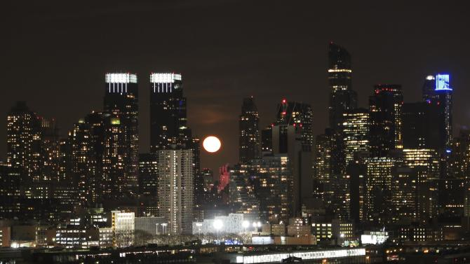 The moon rises behind the skyline of New York, as seen from Weehawken, New Jersey