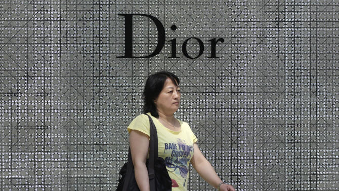 A woman walks by a Dior brand shop, Wednesday June 13, 2012 in Shanghai, China. Chinese consumers can afford to splash out more on higher quality products, but also expect better value for money than in the past, according to a study by the American Chamber of Commerce. (AP Photo/Eugene Hoshiko)