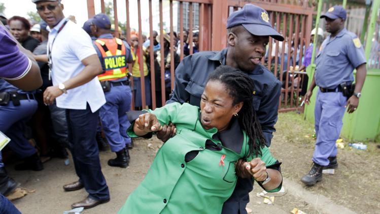 A policeman assists a mourner who fell during a stampede while running to queue before boarding a bus to take her to the Union Buildings in Pretoria