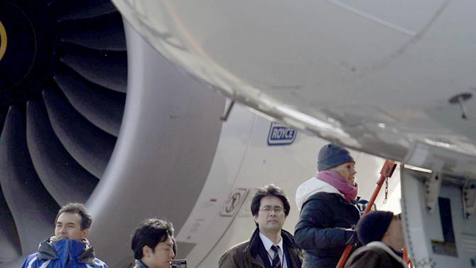 U.S. officials inspect a All Nippon Airways jet which made an emergency landing Wednesday, at Takamatsu airport in Takamatsu, western Japan, Friday, Jan. 18, 2013. An official with Japan's transport safety board says four U.S. officials, including two Boeing Co. representatives, have arrived at the airport in western Japan to inspect the troubled Boeing 787 jet. (AP Photo/Kyodo News)  JAPAN OUT, MANDATORY CREDIT, NO LICENSING IN CHINA, HONG KONG, JAPAN, SOUTH KOREA AND FRANCE