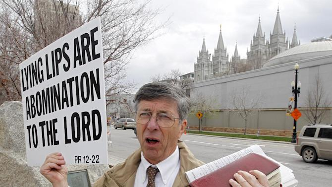 A unidentified man who called himself Brother Carl carries a sign outside the Conference Center during the 183rd Annual General Conference of The Church of Jesus Christ of Latter-day Saints Saturday, April 6, 2013, in Salt Lake City.  More than 100,000 members of the church have gathered in Salt Lake City to hear words of inspiration and guidance for daily living from the faith's senior leaders.  (AP Photo/Rick Bowmer)