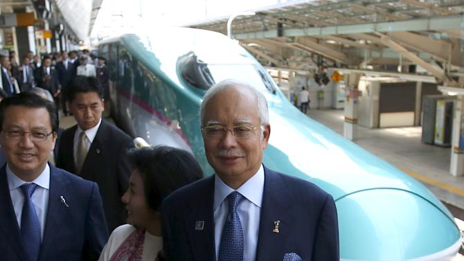 Malaysia's Prime Minister Najib Razak , accompanied by his wife Rosmah Mansor, smiles before he boards to a Shinkansen bullet train bound for northern Japan, at Tokyo Station in Tokyo
