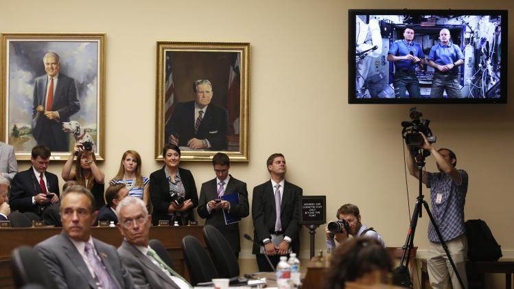 Members of the House Science, Space, and Technology Committee watch a live downlink with U.S. astronauts Wiseman and Swanson aboard the International Space Station (ISS), on Capitol Hill in Washington