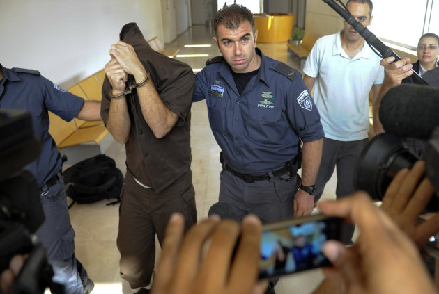 Arab citizen of Israel Milad Khatib covers his face as he is escorted at the district court in the northern Israeli city of Haifa, Thursday, Oct. 4, 2012. Israeli authorities on Thursday indicted an Arab citizen of Israel on charges of spying for the Lebanese militant group Hezbollah, accusing him of gathering intelligence on security for Israel&#39;s president and on army installations. (AP Photo/Abdullah Shama) ISRAEL OUT NOT FOR ARCHIVAL USE