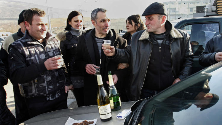 Relatives drink with former prisoner Vano Sabashvili, center, celebrating his freedom at Gldani prison No. 8 in Tbilisi, Georgia, Sunday, Jan. 13, 2013. Nearly 200 inmates considered political prisoners by Georgia's new parliament have walked free under an amnesty strongly opposed by President Mikhail Saakashvili. Many of those who walked free on Sunday were arrested during anti-Saakashvili protests in May 2011. Others had been convicted of trying to overthrow the government or of spying for Russia. (AP Photo) Shakh Aivazov