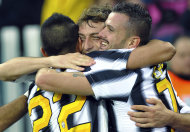 Juventus midfielder Claudio Marchisio, center, celebrates after scoring with his teammates Arturo Vidal, left, and Simone Pepe, during a Serie A soccer match between Juventus and Cesena at the Juventus stadium in Turin, Italy, Sunday, Dec, 4 2011. Juventus won 2-0. (AP Photo/Massimo Pinca)