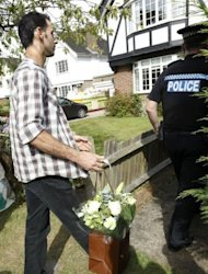 A man delivers flowers at the residential address believed to be the British home of a family shot dead in their car in the French Alps, in Claygate