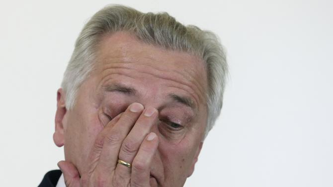 Hundstorfer rubs his eye during a news conference on the pension system in Vienna