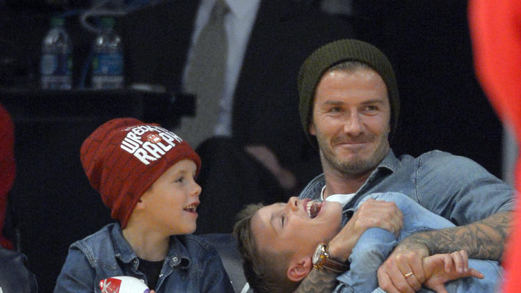 Soccer player David Beckham hugs his son Romeo, right, as his other son Cruz looks on as they watch the Los Angeles Lakers play the Phoenix Suns in their NBA basketball game, Friday, Nov. 16, 2012, in Los Angeles. The Lakers won 114-102. (AP Photo/Mark J. Terrill)