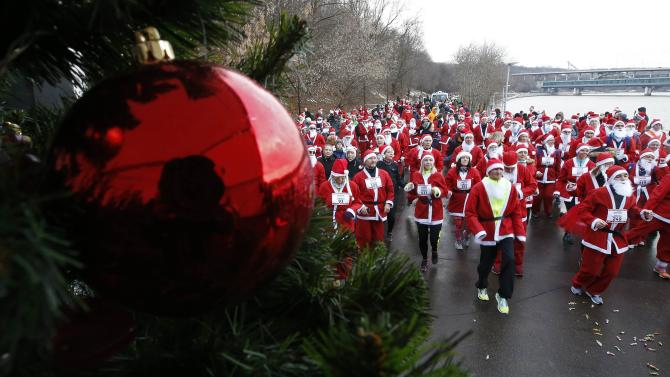 People dressed as Santa Claus and the Russian equivalent Father Frost warm up near a Christmas tree before running in a charitable race in Moscow