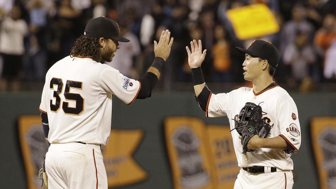 San Francisco Giants shortstop Brandon Crawford (35) and right fielder Nori Aoki celebrate after the Giants beat the Milwaukee Brewers in a baseball game in San Francisco, Monday, July 27, 2015. The Giants won 4-2. (AP Photo/Jeff Chiu)