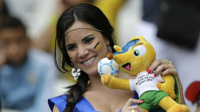 A Brazil supporter smiles holding a toy of mascot 'Fuleco' before the World Cup semifinal soccer match between Brazil and Germany at the Mineirao Stadium in Belo Horizonte, Brazil, Tuesday, July 8, 2014. (AP Photo/Matthias Schrader)