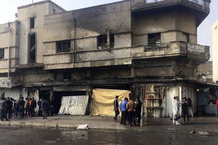 People gather at the scene of bomb attack in Baghdad