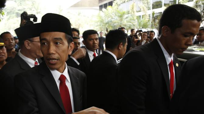 Indonesia's president-elect Joko Widodo gestures after a ceremony inaugurating a new parliament in Jakarta