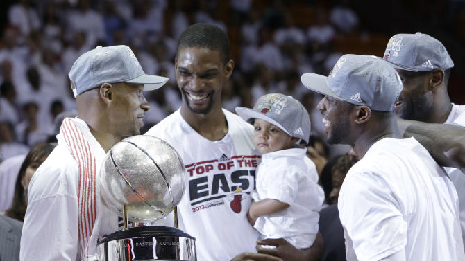 Miami Heat's Ray Allen, left, holds the NBA Eastern Conference trophy as Chris Bosh hold his son Jackson and Dwyane Wade and LeBron James smile, Monday, June 3, 2013, in Miami. The Heat defeated the Indiana Pacers 99-76 to advance to the NBA Finals against the San Antonio Spurs. (AP Photo/Lynne Sladky)