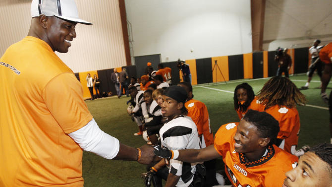 Lancaster senior running back Jaelyn Carr greets Dallas defensive lineman DeMarcus Ware before practice Tuesday, Nov. 13, 2012inLancaster, Texas. DeMarcus joined Duracell Trust Your Power program to encourage youth to realize their power to achieve their goals. (Photo by Brandon Wade/Invision for Duracell/AP Images)