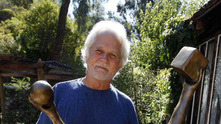 "In this Thursday, Sept. 18, 2012 photo, Tony Dow, actor, director and artist, poses with one of his works at his home and studio in the Topanga area of Los Angeles. When it comes time to sitting down in a studio and carving out bronze and wooden sculptures inspired by the nature all around him, Wally isn't leaving it up to the Beav these days. Dow, who famously played the Beaver's older brother Wally on the classic 1950s-60s sitcom ""Leave it To Beaver,"" is carving out a name for himself in the art world these days, as an abstract artist. (AP Photo/Reed Saxon)"