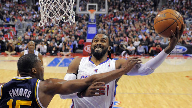 Los Angeles Clippers center Ronny Turiaf puts up a shot as Utah Jazz forward Derrick Favors defends during the first half of an NBA basketball game, Sunday, Dec. 30, 2012, in Los Angeles. (AP Photo/Mark J. Terrill)