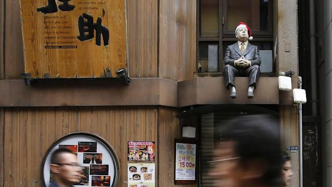 A lifesized doll, adorned with a Santa hat, is seen above the doorway of a restaurant as people walk along a street at Tokyo's Shinjuku shopping and business district