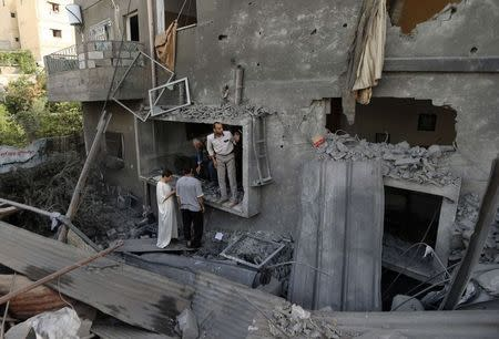 alestinians survey a house which police said was damaged in an Israeli air strike on a neighbouring house in the northern Gaza Strip