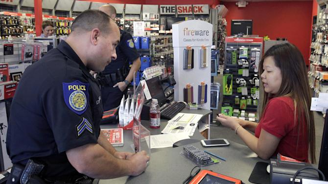 In this Nov. 12, 2012, photo, Sacramento Police Officer Erik Farahmand interviews store manager Katie Vang about merchandise stolen during an overnight break-in at a Radio Shack store in Sacramento, Calif. Sacramento voters, who don't want to see a reduction in service such as public safety, approved a sales tax hike by a 2-to-1 ratio. During last week's elections, voters across the country opted to raise taxes to help their cities, counties and school districts. (AP Photo/Rich Pedroncelli)