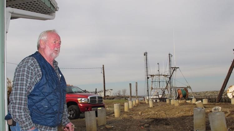 In this Dec. 12, 2012 photo, Joe Branin, manager of the Belford Seafood Co-op in Midletown N.J., walks across sand where the commercial fishing port's dock used to be before Superstorm Sandy destroyed it, leaving only rows of support pilings. The port sustained nearly $1 million in damages from the storm, some of which its owners hope to recoup through federal storm aid. (AP Photo/Wayne Parry)