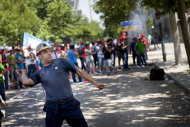 <p>               A miner throws a firecracker at the Industry Ministry during a demonstration to protest against cuts in Madrid, Thursday, May 31, 2012. Miners coming from all around Spain demonstrate in Madrid amid fear on losing their jobs. Spain is moving closer to the financial tipping-point that could force it to ask for a bailout as the country's borrowing costs neared unsustainable levels Wednesday. The country's economic fortunes have gone from boom to bust over the past decade.(AP Photo/Daniel Ochoa de Olza)