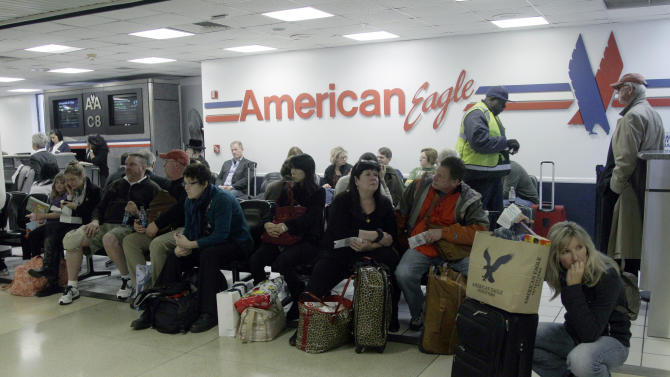 Passengers wait for their flight at at LaGuardia airport, Sunday, Oct. 28, 2012 in New York. Tens of thousands of residents were ordered to evacuate coastal areas Sunday as big cities and small towns across the Northeast buttoned up against the onslaught of a superstorm (AP Photo/Mary Altaffer)