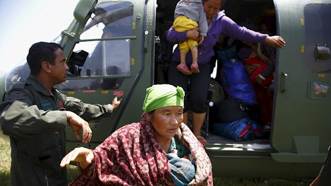 A mother carrying her 22 day-old infant alights from an helicopter after being airlifted from Sindhupalchok District, following last week's earthquake in Nepal