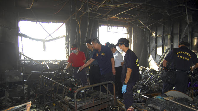 In this photo released by Tainan Fire Department, investigation teams search for possible causes of an early morning fire that swept through the Hsinying Hospital's nursing ward, early Tuesday, Oct. 23, 2012, in the southern city of Tainan, Taiwan. Officials say the fire has killed 12 patients and injured 70 others. (AP Photo/Tainan Fire Department) EDITORIAL USE ONLY