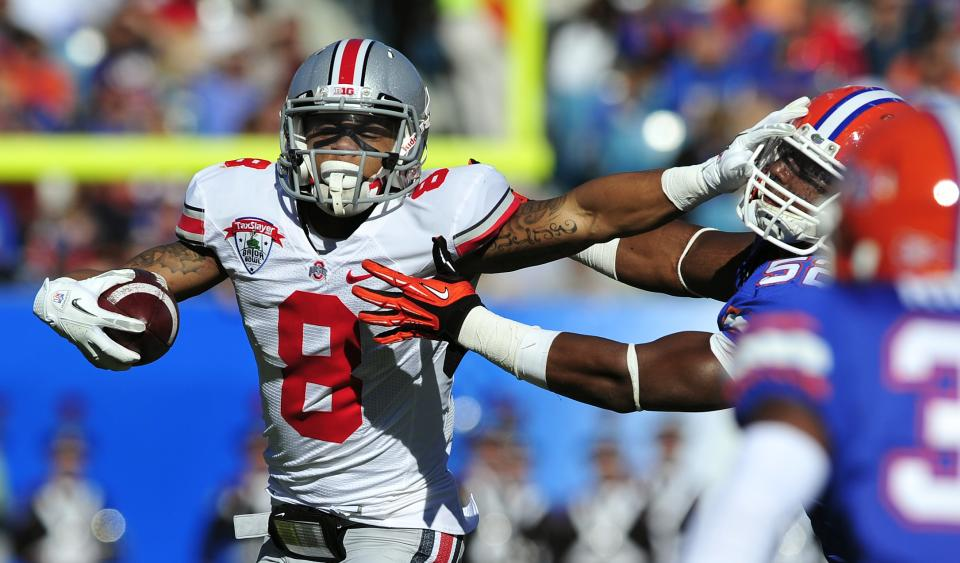 Ohio State wide receiver DeVier Posey (8) stiff arms Florida linebacker Jonathan Bostic (52) during the first half of the Gator Bowl NCAA college football game, Monday, Jan. 2, 2012, in Jacksonville, Fla. (AP Photo/Stephen Morton)